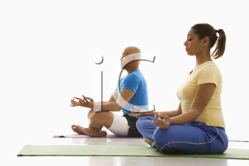 Side view of mid adult multiethnic man and woman sitting in lotus position on exercise mats with eyes closed and legs crossed.
