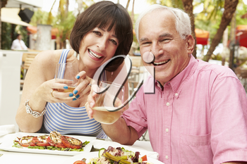 Senior Couple Enjoying Meal In Outdoor Restaurant Together