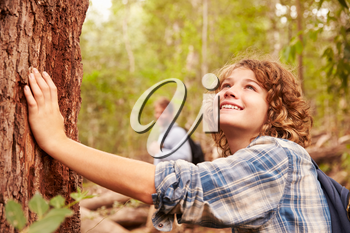 Boy touching a tree in a forest, his father in the background