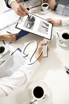 Above angle of businesspeople's hands holding documents, papers with cups of coffee near by