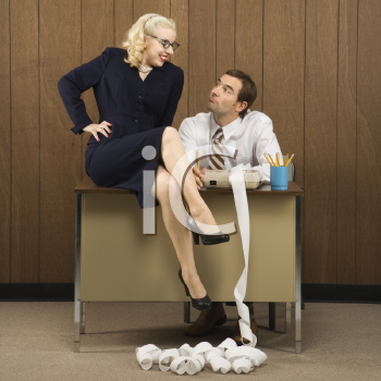 Royalty Free Photo of a Man Sitting at a Desk Looking at a Woman Sitting on the Desk