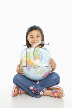 Asian girl sitting on floor holding Earth globe in her lap.