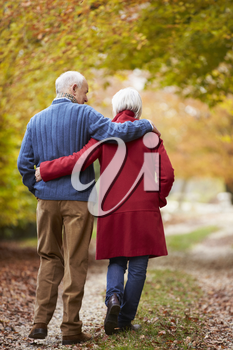 Rear View Of Senior Couple Walking Along Autumn Path