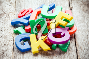 Pile of colorful plastic letters on wooden background
