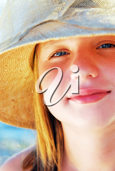 Portrait of a teenage girl wearing a straw hat  on a beach