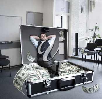 Happy businessman sits in the case full of dollars in the office